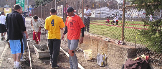 Tiger Pause working on sidewalk behind track and soccer field.